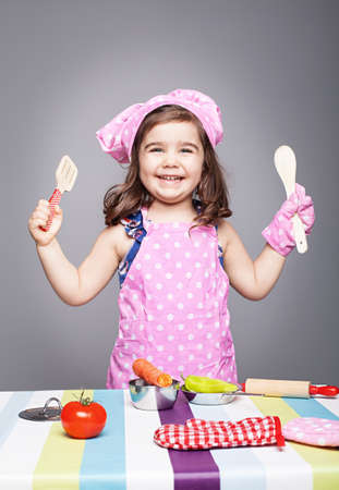 adaorable little chef smiling and holding wooden spoons