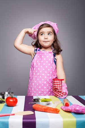 ni�os cocinando: peque�o cocinero en uniforme rosa pensar qu� cocinar Foto de archivo