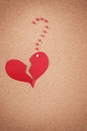 memorise: broken heart and a question mark made of paper and tacks on corkboard