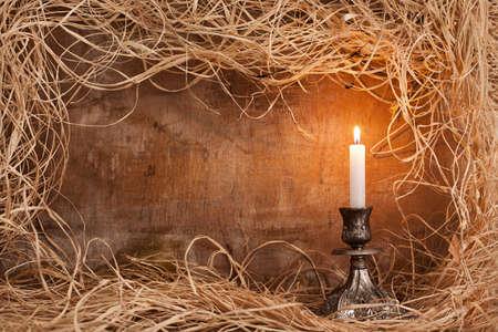 single candle burning on candle holder on grunge wooden background with straws