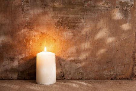 lit candle: single candle light on grunge background.still life