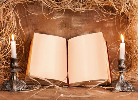 open book with blank pages and 2 candles on grunge background photo