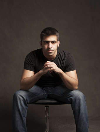 young man with casual clothes sitting on a chair with on grunge background photo