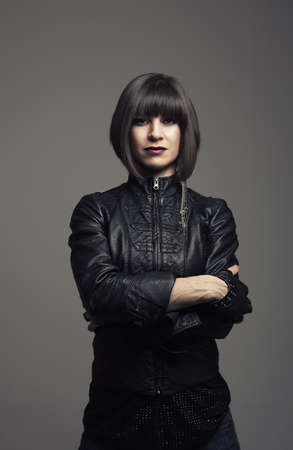 rebellious: beautiful young woman waering leather jacket looking at camera Stock Photo