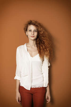 red hair woman: young beautiful girl with curly long hair looking at camera on orange background