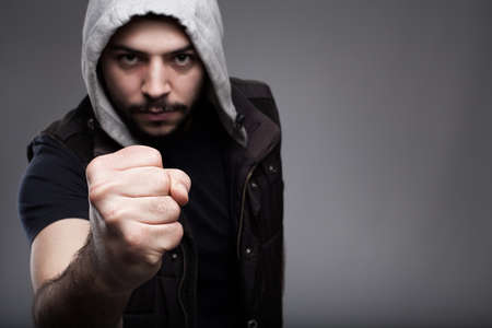 determined: angry young man challenging.shallow depth of field where fist in focus and models face is out of focus.