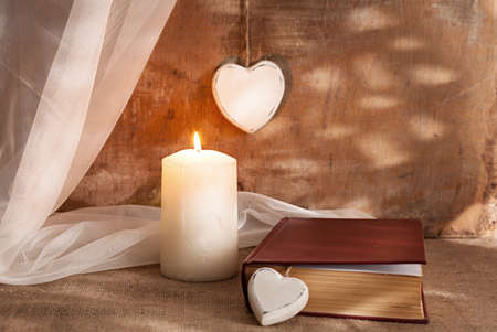 still life photo with a wooden hearts,candle,book and a pile fabric.shallow depth of field where candle is in focus. photo