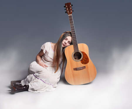 60s hippie: young beautiful hippie sleeping and dreaming with her head on her guitar. Stock Photo