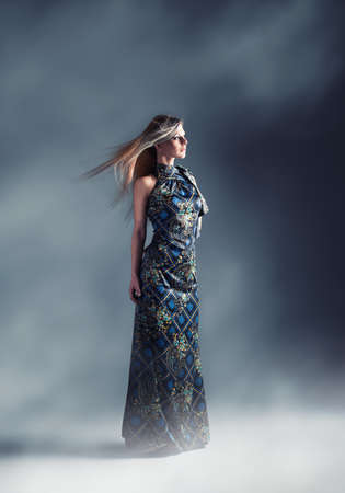 flowing hair: young beautiful model posing with a blue long night dress with fog around