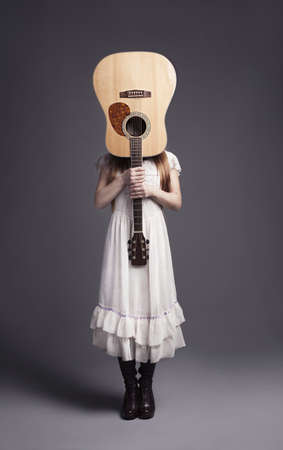 young girl in white dress holding a guitar in fornt of her head photo