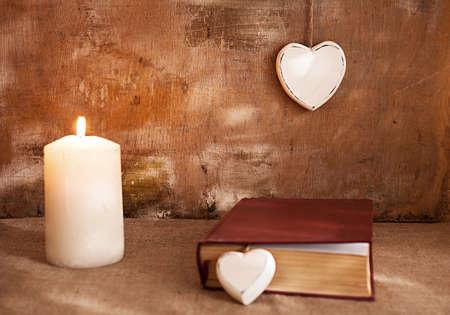bougie coeur: concept avec une bougie coeurs en bois et un livre sur la vie grunge background.still