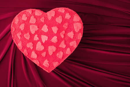 new love: red heart shaped gift box on red fabric Stock Photo