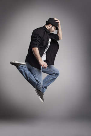 breakdance: young man jumping high and holding his hat on grey background