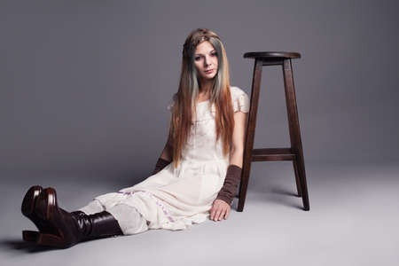 sitting down: hippie like young lady sitting down on the floor with a stool next to her