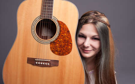 smiling hippie girl posing with her guitar photo