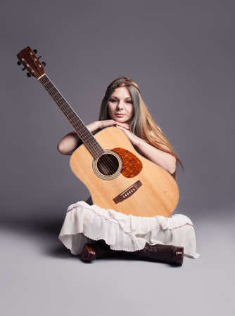 guitarists: hippie girl with her guitar on gray background