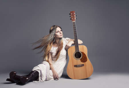 young girl looking like a hippie with guitar on grey background photo