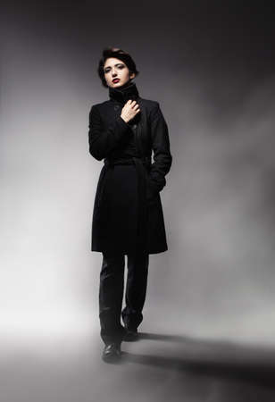 beautiful young model wearing a topcoat walking in misty environment photo