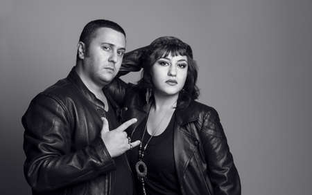 young rocker couple with leather jackets posing and looking at camera photo