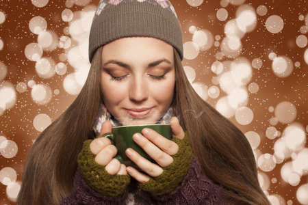 long haired young woman relaxing and warming with cup of coffee or tea brown background with bokeh and sparkles photo