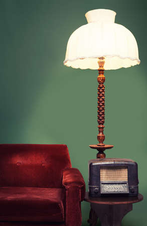 decoration with vintage sofa,shade lamp and a radio on green background photo