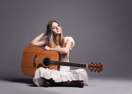hippie girl with her guitar smiling and looking at camera photo