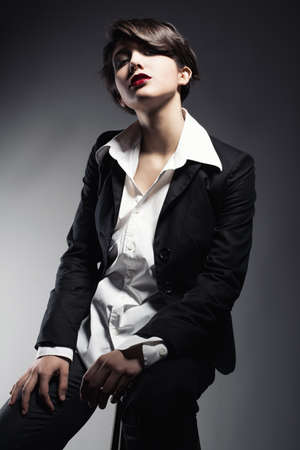 snobbish young girl in suit looking at camera on dark background. photo