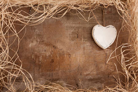 single white heart on grunge wooden background with straws  Stock Photo
