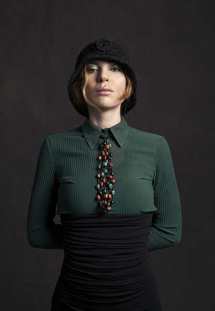 strict lady with retro style clothes looking at camera on grunge background photo