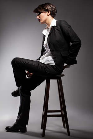 young model with wearing suit sitting on a stool on grey background photo