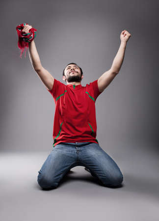 fan: happy supporter with his hands up posing  Stock Photo