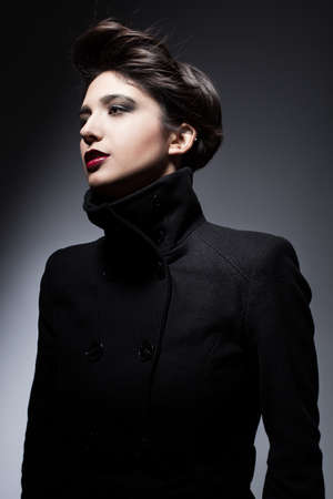young woman with flying black hari wearing a topcoat and posing on dark background photo