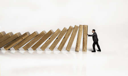 domino effect: businessman is trying to prevent the falling