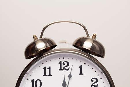 alarm clock is ringing at twelve on white backround photo