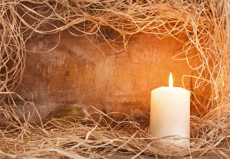 frame with single candle,straw and textured wooden background photo
