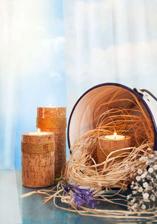 candle holders: still life with wooden candle holders,candles,straw,flowers and a vintage bucket