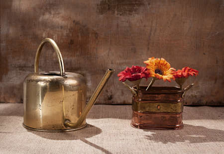 ewer made of brass and colorful flowers in copper flowerpot on grunge background photo