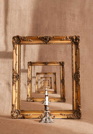 golden picture frame and white candle repating on grunge background photo