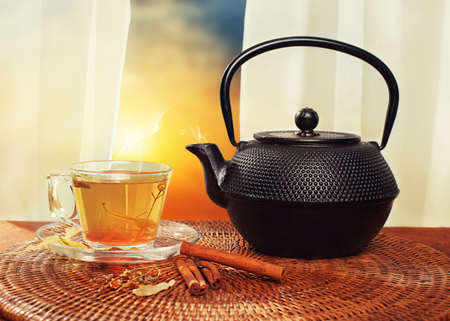 organic concept: organic concept with herbal tea and a retro teapot with sun and clouds in background Stock Photo
