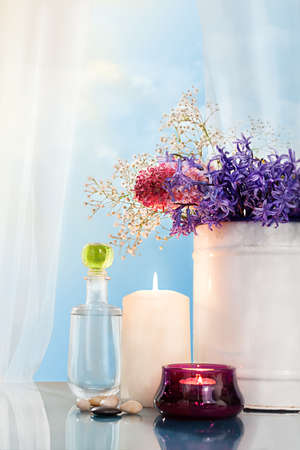 window treatments: still life with various flowers and a bottle of liquid in front of an open window