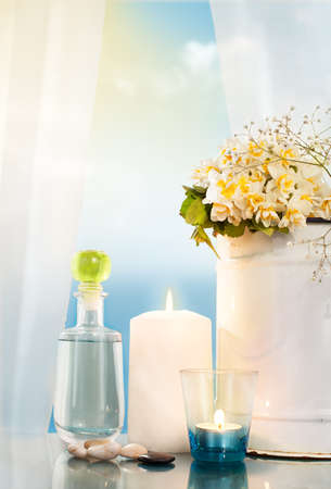 burning candles, bucket and a bottle in front of a window with open curtain with sky and sea in background photo