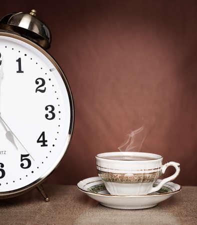 tarde de cafe: stilllife Concpet imagen de la taza de té y un reloj de alarma sobre fondo marrón
