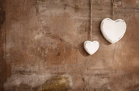 two white hearts made of wood in different sizes on grunge background Stock Photo