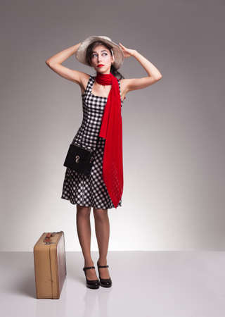 heel strap: young lady wearing vintage clothes and hat,standing near her  retro suitcase and  waiting her vehicle to arrive Stock Photo
