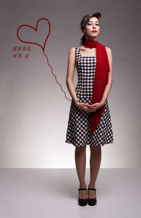 checkered scarf: young cute lady holding a drawing balloon looking at camera on grey background