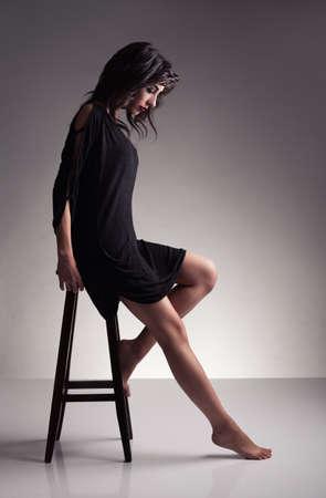 escabeau: proflie d'un mod�le de jeune brunette avec pieds nus, regardant vers le bas sur fond gris