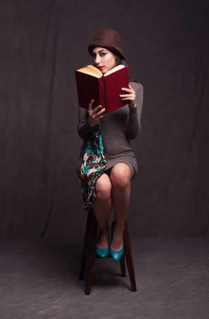 young brunette model holding a opne book and looking at camera behind it on grunge background photo