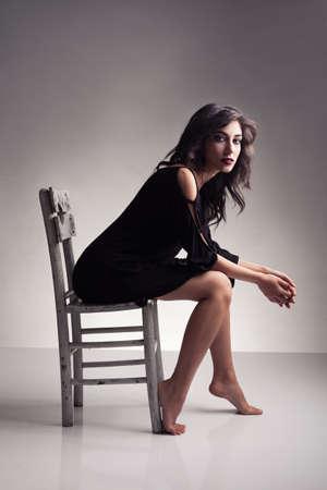 donna seduta sedia: interessante modello bruna, seduta su una vecchia sedia in posa e guardando la fotocamera su sfondo grigio