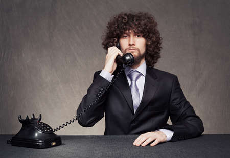 serious businesmann with afro style hair answering the retro phone on grunge background Stock Photo - 18617291