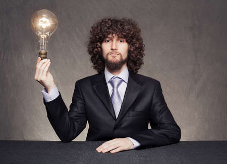 serious afro style haired businessman wearing a suit holding a bulb on grunge background